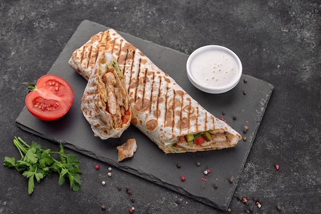 Shawarma mit fleisch, cutaway, mit sauce, tomaten, käse, kräutern und knoblauch, auf schwarzem schiefer