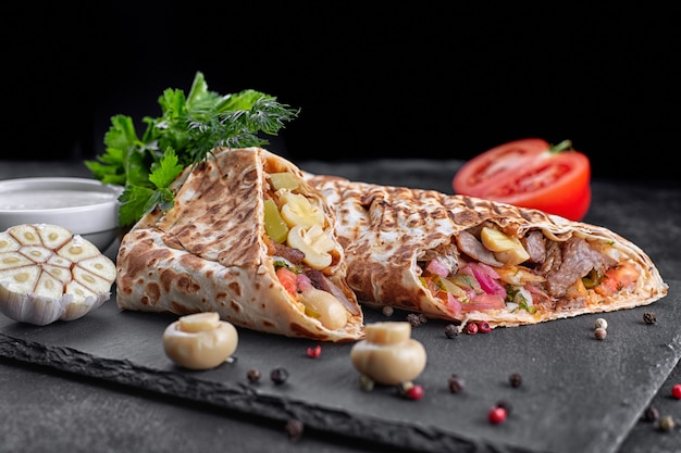 Shawarma mit fleisch, mit sauce, zwiebeln, gurken, tomaten, knoblauch, kräutern und pilzen champignons, auf schiefer, vor einem dunklen betonhintergrund