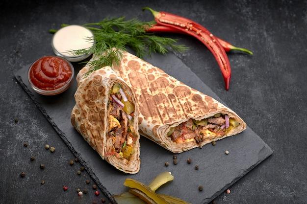 Shawarma mit kalbfleisch, mit sauce, zwiebeln, gurken, kräutern und scharfem rotem pfeffer, auf schiefer, vor einem dunklen betonhintergrund
