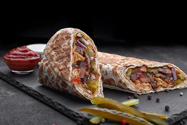 Shawarma mit kalbfleisch, mit sauce, zwiebeln, gurken, kräutern und scharfem rotem pfeffer