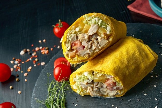 Shawarma oder burrito brötchen mit huhn, ananas, tomaten und salat. straßenessen