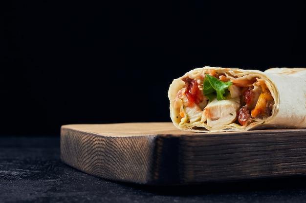 Shawarma-sandwich. frische rolle von dünnem lavash gefüllt mit hühnerfleisch, käse, grün auf tisch.