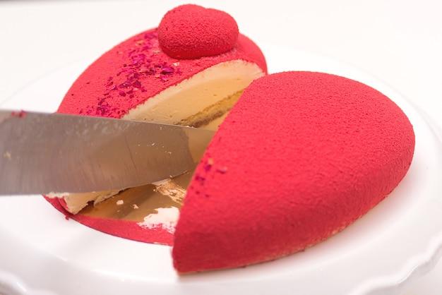 Shef schneidet festlichen kuchen. roter luxusmoussekuchen verziert mit rosen.