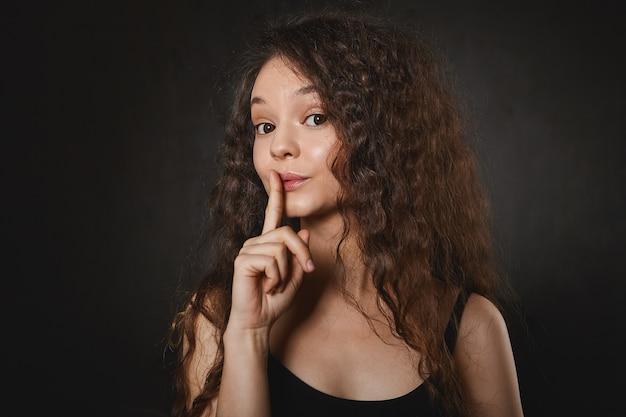 Shh. erzähl es niemandem. bild des emotionalen lustigen brünetten mädchens im trägershirt, das vorder ingwer an ihren lippen hält, augenbrauen hochzieht, shh sagt und bittet, ihr geheimnis nicht preiszugeben. vertrauliche informationen