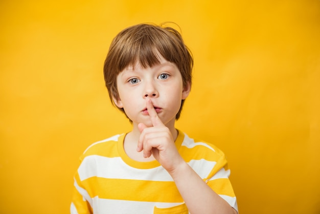 Shh, halte das konzept still. junge kaukasische kinderjunge gestikuliert, stille-schilderstellung über gelbem hintergrund isoliert. studioaufnahme. finger auf den lippen, stille geste, geheim. platz kopieren