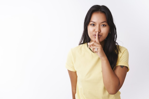 Shh halte es geheim. porträt einer mysteriösen und süßen tätowierten jungen vietnamesischen frau der 20er jahre im t-shirt, die sich vor der kamera schüttelt, um überraschung zu verbergen, zu flüstern, vor weißem hintergrund zu posieren