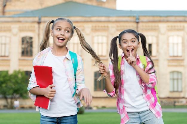 Shh mädchen geheim. glückliche kinder halten ein geheimnis. kleines mädchen macht geheime geste. freunde und freundschaft. stille und stille. zurück zur schule. ausbildung und studium. tag des wissens. wir haben unser kleines geheimnis.