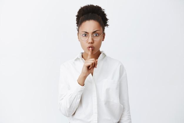 Shh, ruhig, stille im unterricht. strenge und ernsthaft aussehende dunkelhäutige lehrerin in weißem hemd und brille, die mit dem zeigefinger über dem mund eine shush-geste macht und verlangt, die stimme leise zu halten