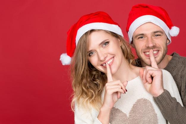 Shh santa ist da! horizontales porträt eines jungen glücklichen paares, das weihnachtsmützen trägt, die stillende geste machen