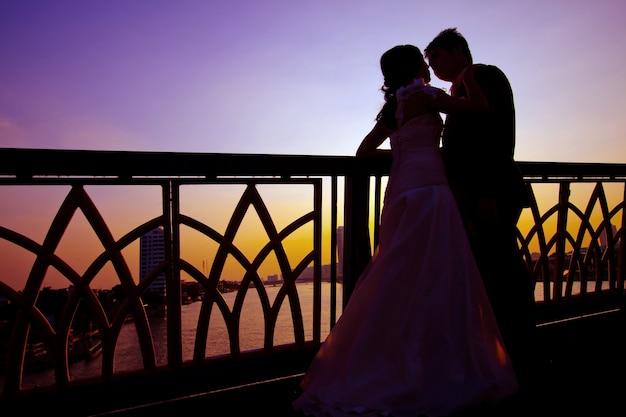 Shilhouette von romantischen und glückspaaren auf der brücke über dem fluss
