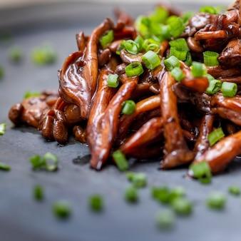 Shimeji-pilz serviert mit schnittlauch auf schwarzer steinplatte. typisch orientalisches essen. detail der speiseschale, nahaufnahme, selektiver fokus.