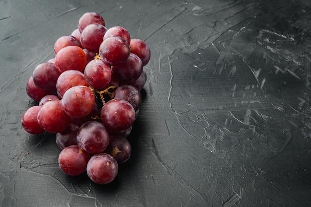 Shine traubenfruchtset, dunkelrote früchte, auf schwarzem steintisch