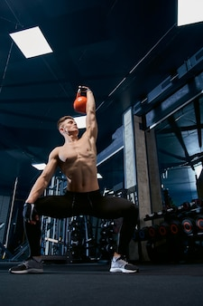Shirtless bodybuilder training mit gewichten.