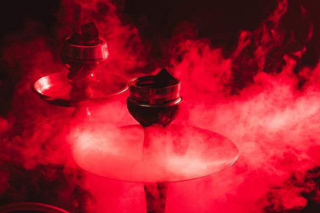 Shisha bowl, shisha und kohlen nahaufnahme auf einem rauchigen schwarzen hintergrund mit farbiger beleuchtung