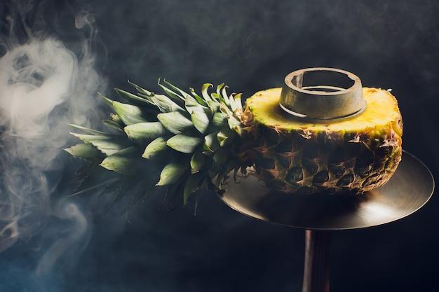 Shisha heiße kohlen auf shisha schüssel mit schwarzem hintergrund. stilvolle orientalische shisha. ananas