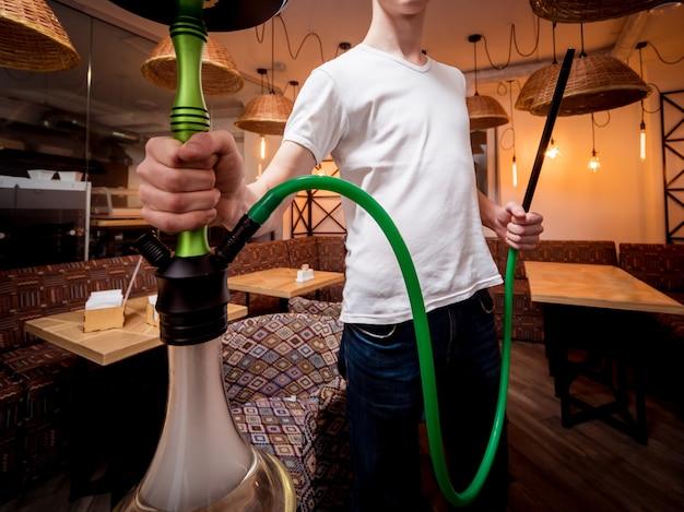 Shisha in der bar kochen. junger mann mit wasserpfeife im restaurant, wasserpfeifenbar, rauchendes café.