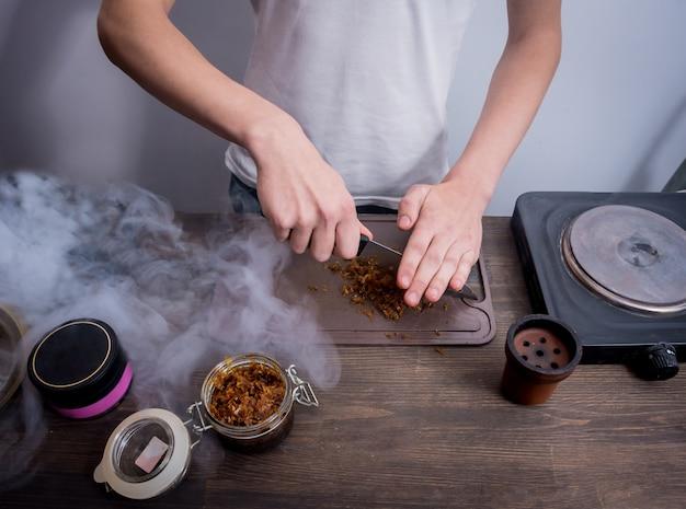 Shisha in der bar kochen. tabak in eine schüssel schneiden. restaurant, shisha-bar, raucher-café.