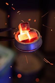 Shisha-schüssel mit erhitzten kohlen, partikel fliegen herum