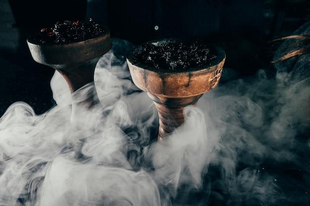 Shisha-schüssel mit handwerkstabak und roter kohle mit blauem und rotem rauchhintergrund der huka