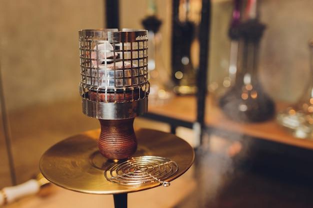 Shisha shisha mit glühenden kohlen. funken vom atmen. moderne wasserpfeife mit kokosnusskohle und shisha-rauch. wasserpfeife und funken aus kohlen., traditionelle heiße wasserpfeifen zum rauchen von natürlichem licht.