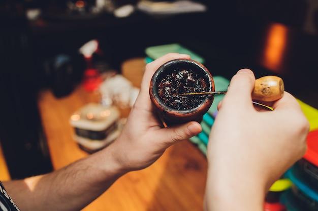 Shisha zum rauchen vorbereiten, tonschale mit tabak füllen, männliche hände sichtbar.