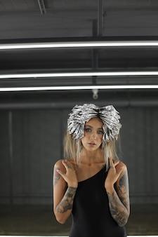 Shooting ein schönes model-mädchen mit tattoos auf ihrem körper und silberfolie auf ihrem kopf, um ihr haar zu färben urban fashion shooting hochwertiges foto