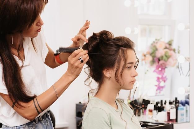 Shooting in einem schönheitssalon. der haarmeister korrigiert die frisur eines jungen dunkelhaarigen mädchens mit hilfe einer haarbürste.