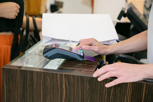 Shop kassierer betrieb zahlungsvorgang mit pos terminal und kreditkarte. kurzer schuss, nahaufnahme der hände. einkaufs- oder kaufkonzept