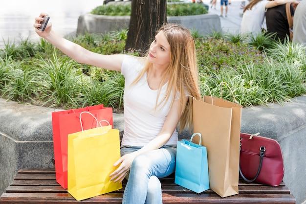 Shopaholic frau, die auf der bank nimmt selfie auf smartphone sitzt
