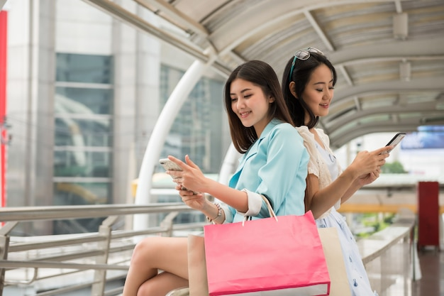 Shopaholic-freunde spielen smartphone in der stadt