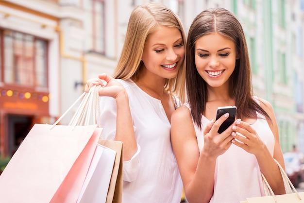 Shopaholic-freunde. zwei attraktive junge frauen, die einkaufstaschen halten und zusammen auf das handy schauen, während sie im freien stehen