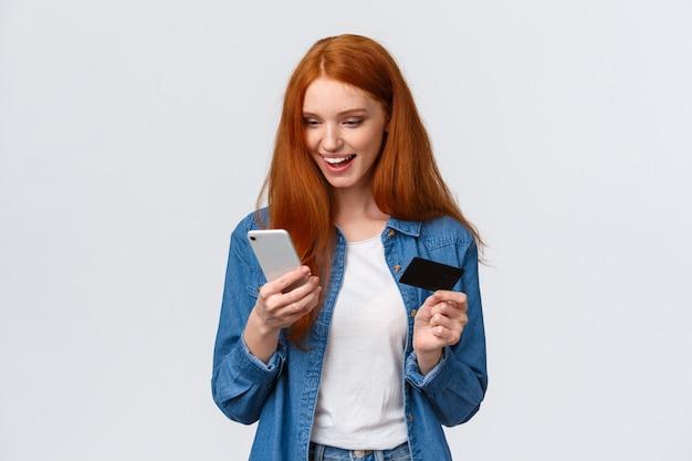 Shopaholic, internet-konzept. nette freundliche rothaarigefrauenbestellung des oberkörperporträts online, fügen bankdatenregister vor ort, taxibestellungsantrag, griffkreditkarte und smartphone ein und lächeln