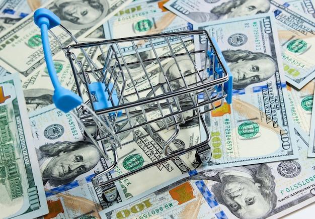 Shopaholic-konzept. einkaufswagen auf dem hintergrund von hundert dollarnoten