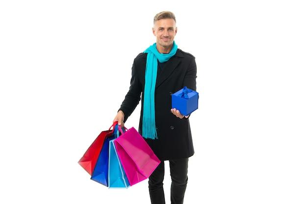 Shoppen sie immer mehr. glücklicher kerl hält papiertüten und geschenkbox. geschenkeladen. black friday-verkauf. einkaufen macht spaß.