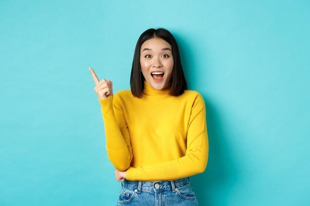 Shopping-konzept. attraktive koreanische frau, die erstaunt lächelt, mit dem finger nach links zeigt, ein gutes deal-banner zeigt und vor blauem hintergrund steht