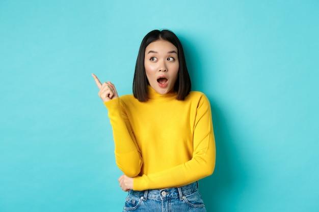 Shopping-konzept. beeindrucktes asiatisches mädchen in gelbem pullover, zeigt und schaut erstaunt nach links, zeigt logo-banner, steht auf blauem hintergrund