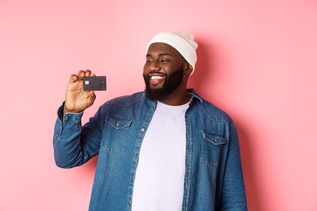 Shopping-konzept. bild eines glücklichen afroamerikanischen mannes, der zufrieden auf die kreditkarte schaut, die bank empfiehlt und über rosafarbenem hintergrund steht.