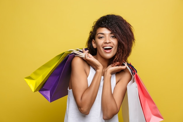 Shopping-konzept - close up portrait junge schöne attraktive afrikanische frau lächelnd und freudig mit bunten einkaufstasche. gelbe pastellwand hintergrund. text kopieren