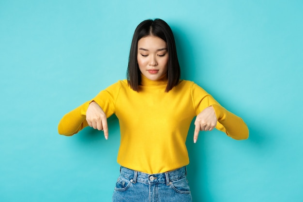 Shopping-konzept. junges koreanisches mädchen im teenageralter, das auf die werbung zeigt und auf sie schaut, vor blauem hintergrund stehend