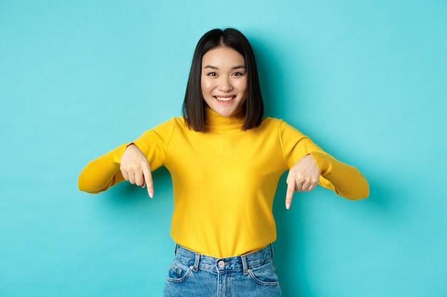 Shopping-konzept. schönes koreanisches mädchen mit glücklichem lächeln, das mit den fingern nach unten auf das banner zeigt und vor blauem hintergrund steht.