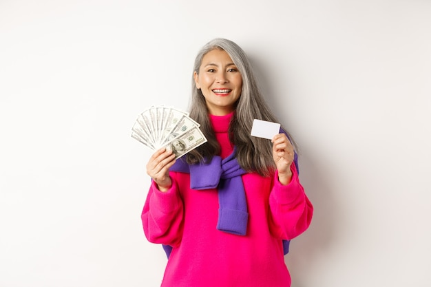 Shopping-konzept. stilvolle asiatische ältere frau mit grauem haar, gelddollar und plastikkreditkarte zeigend, stehend über weißem hintergrund.
