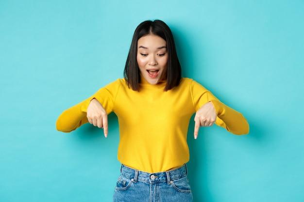 Shopping-konzept. überraschtes süßes asiatisches mädchen, das rabatte auscheckt, mit den fingern nach unten zeigt und erstaunt aussieht, wow sagt und auf blauem hintergrund steht.