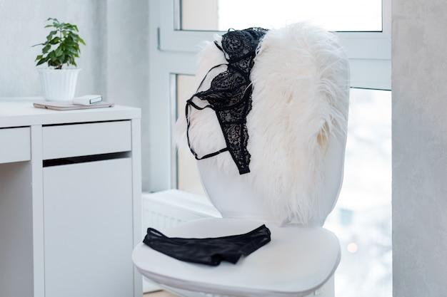 Shopping und mode, weibliches garderobenkonzept. satz glamouröser stilvoller sexy spitzenwäsche auf weißem stuhl, dachbodeninnenraum. frauenzubehör