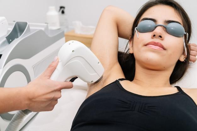 Short shot kosmetikerin, die einer frau in der achselhöhle, in der der kunde eine laserschutzbrille trägt, eine laserdiodenbehandlung gibt