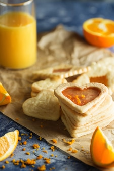Shortbread-kekse mit orangefarbenem zuckerguss in form von herzen auf blau
