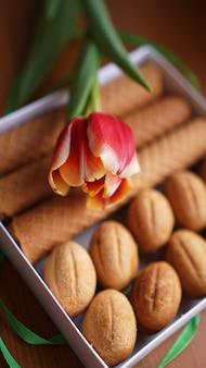 Shortbread-kekse und tulpen. geschenk an die frau. russische süßigkeiten - oreshki-kekse und -röhren - vertikales foto - gutes format für geschichten