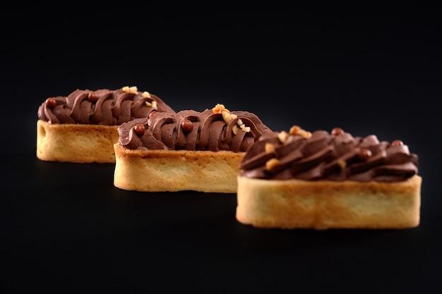 Shortbread-kekskekse mit geschlagener brauner schokoladencreme-mascarpone-belag. drei frische hausgemachte desserts lokalisiert auf schwarzem hintergrund. konzept der süßigkeiten, lebensmittelindustrie.