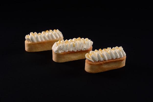 Shortbread-kekskekse mit schlagsahne-mascarpone-belag. drei frische hausgemachte desserts lokalisiert auf schwarzem hintergrund. konzept der süßigkeiten, lebensmittelindustrie.