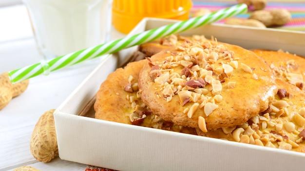 Shortbread-milchkekse mit gehackten nüssen, milch und honig. kekse in einer schachtel. nahansicht