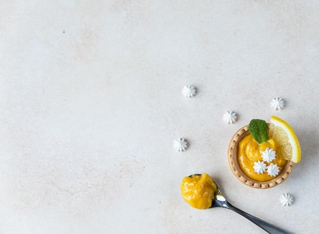 Shortbread mini-tarte mit zitronenquark-minze und zitronenscheiben und mini-baiser